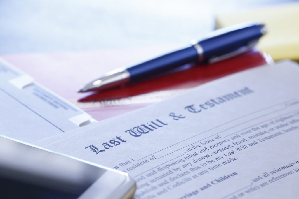 Ballpoint Pen And Mobile Phone Rest On Top Of Last Will And Testament Documents