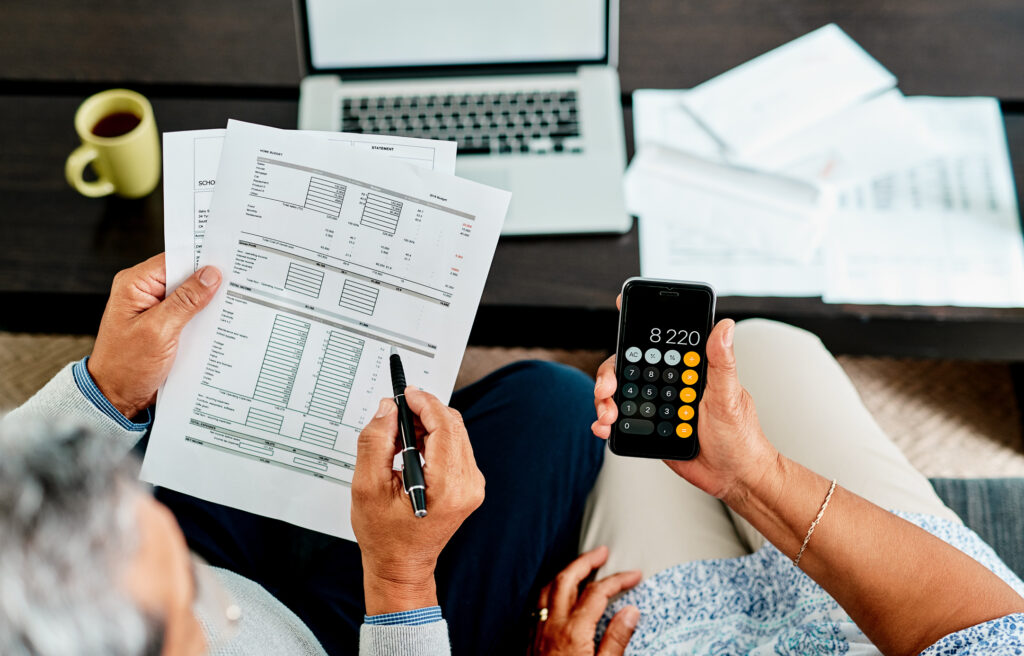 High angle shot of a couple calculating their finances together at home