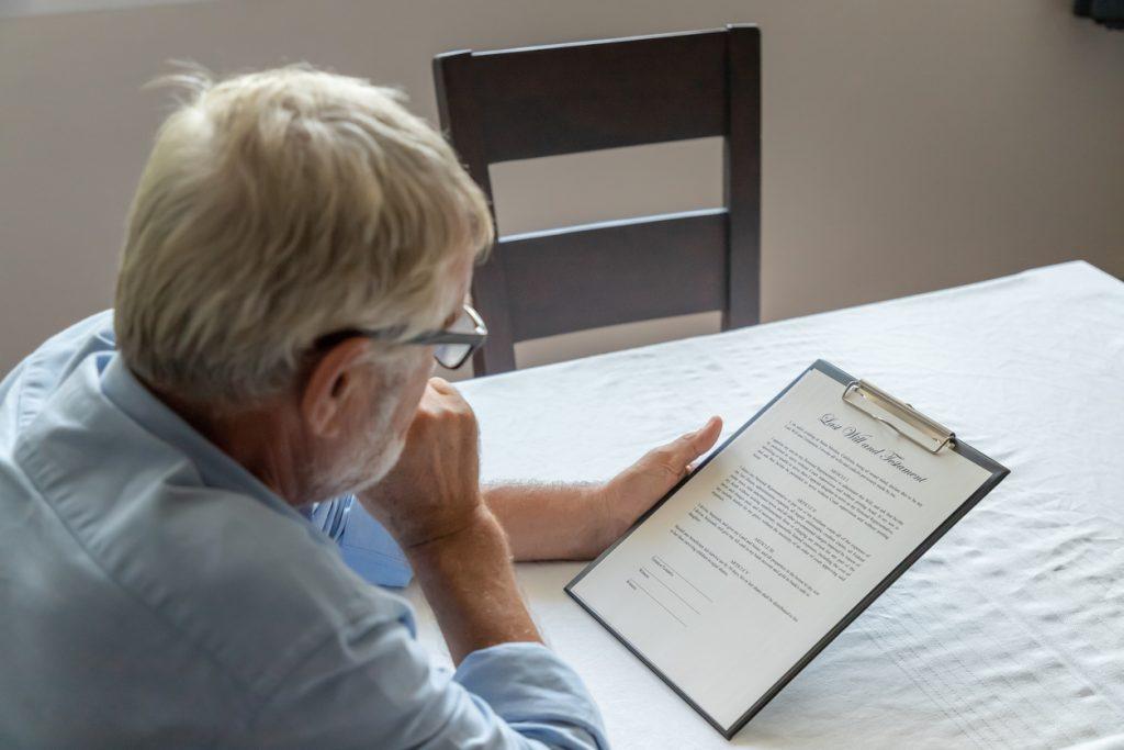 Senior Man Examining Last Will And Testament