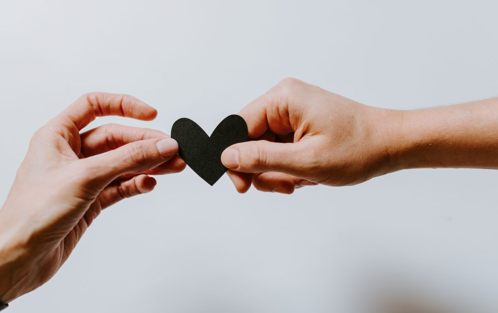 one hand holding black heart giving to other person's hand