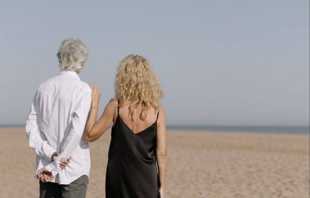 man and woman at a beach looking at water with the woman holding the mans shoulder and the man resting hands behind his back